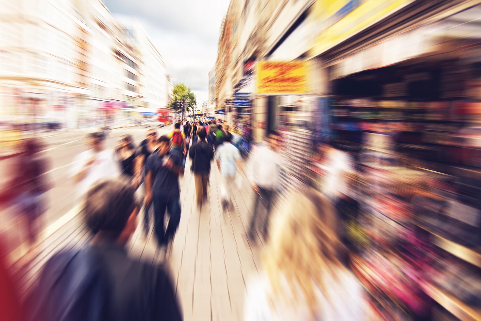 People shopping and walking in London Oxford street - radial zoom effect defocusing filter applied, with vintage instagram look